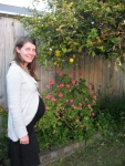 Me, 31 weeks pregnant, in our yard by the lemon tree